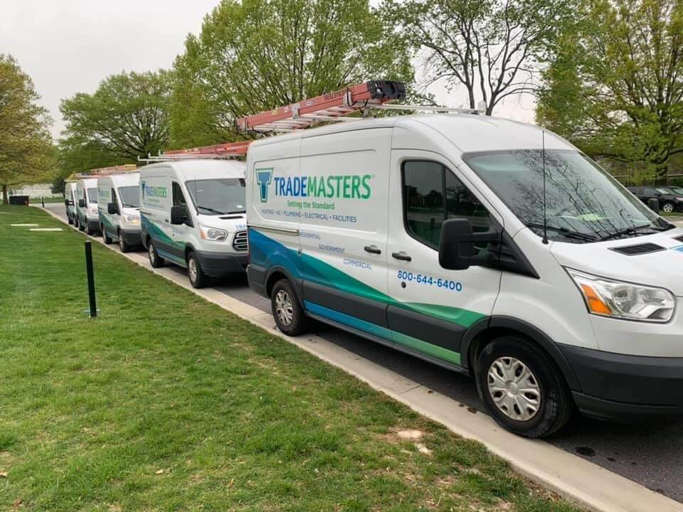 trademasters hvac and plumbing trucks lined up oustside residential home