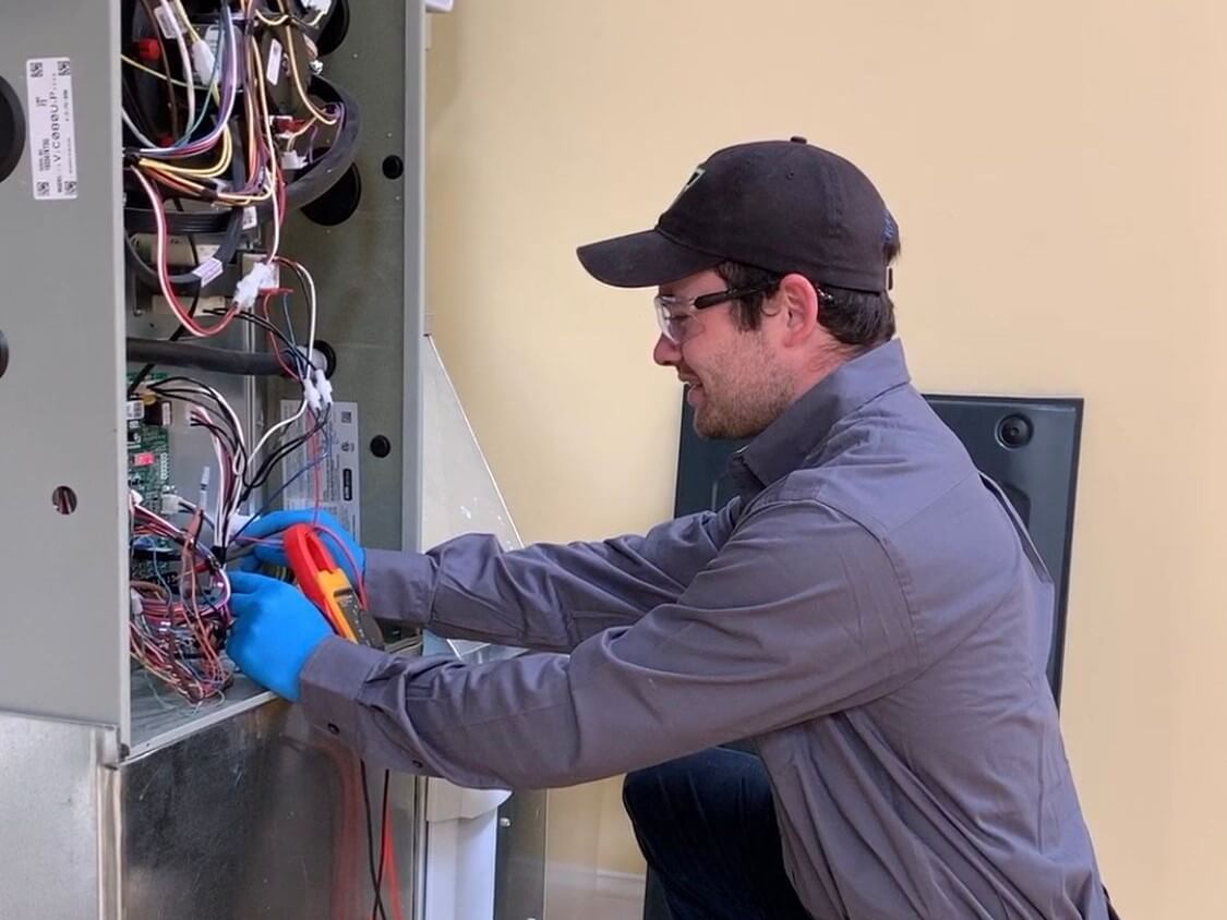 Trademasters HVAC technician servicing a heating system.