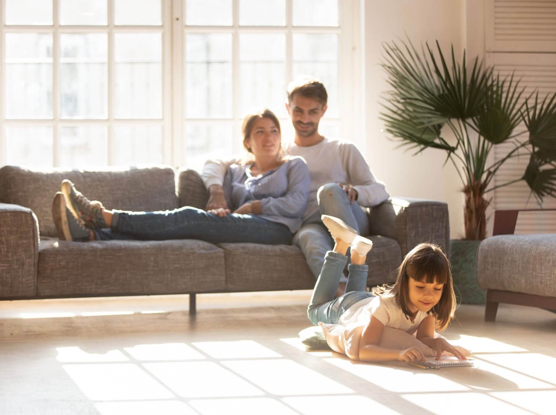 A family relaxing in a sun-drenched living room. The child lays on the floor reading a book while the parents watch happily from the couch.